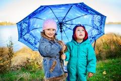 Petite fille et garçon avec le parapluie jouant sous la pluie Les enfants jouent extérieur par le temps pluvieux dans la chute Am Photographie stock libre de droits