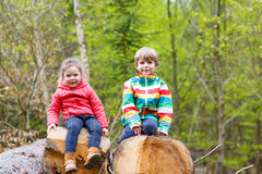 Petite fille et garçon blond mignon jouant ensemble dans la forêt Photographie stock libre de droits