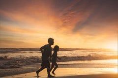 Petite fille et garçon courant sur la plage Photo stock