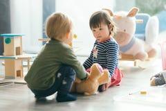 Petite fille et garçon jouant avec des jouets par la maison Photos libres de droits