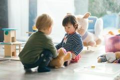 Petite fille et garçon jouant avec des jouets par la maison Photographie stock libre de droits