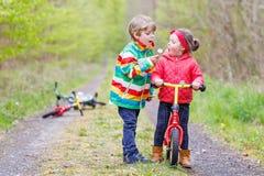 Petite fille et garçon jouant ensemble dans la forêt Images stock