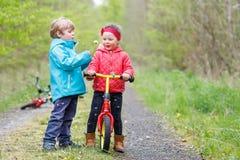 Petite fille et garçon jouant ensemble dans la forêt Photographie stock