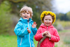 Petite fille et garçon jouant ensemble dans la forêt Images libres de droits