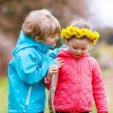Petite fille et garçon jouant ensemble dans la forêt Photo stock