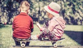 Petite fille et garçon jouant sur la planche à roulettes, contre le contexte Photo libre de droits