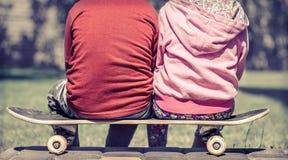 Petite fille et garçon jouant sur la planche à roulettes, contre le contexte Photographie stock