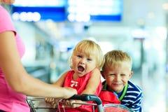 Petite fille et garçon mignons heureux à l'aéroport dessus Images stock