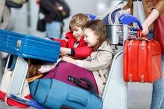 Petite fille et garçon s'asseyant sur des valises sur l'aéroport Image libre de droits