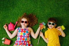 Petite fille et garçon se trouvant sur l'herbe verte Images stock