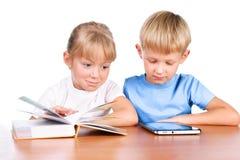 Petite fille et garçon utilisant la garniture et le livre digitaux images stock