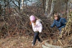 Petite fille et garçon dans le buisson Photo stock