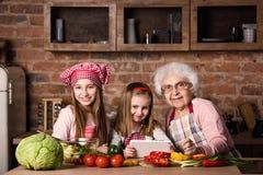 Petite-fille et grand-mère avec le comprimé recherchant la recette Image stock