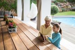Petite-fille et grand-mère discutant au-dessus d'un comprimé numérique Images libres de droits