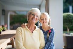 Petite-fille et grand-mère ensemble à une nuance de plate-forme un jour ensoleillé Image stock