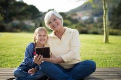 Petite-fille et grand-mère s'asseyant sur la plate-forme avec le comprimé numérique Photo stock