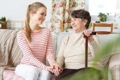 Petite-fille et grand-mère s'asseyant sur un sofa Images stock