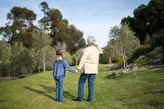 Petite-fille et grand-mère se tenant ensemble dans le jardin Image stock