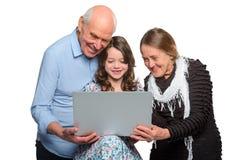 Petite-fille et grands-parents ayant l'appel visuel photographie stock