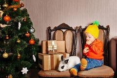 Petite fille et lapin mignons près d'arbre de Noël Photos stock