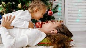 Petite fille et mère étreignant à l'intérieur avec l'arbre de Noël sur le fond Photographie stock libre de droits