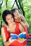 Petite fille et mère affichant le livre. Photographie stock libre de droits