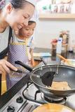 Petite fille et mère asiatiques faisant la crêpe Photos stock