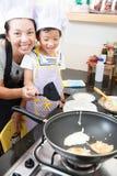 Petite fille et mère asiatiques faisant la crêpe Photos libres de droits