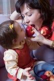Petite fille et mère avec des pommes Photographie stock