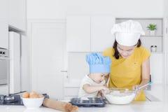 Petite fille et mère faisant le gâteau Photographie stock