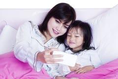 Petite fille et mère prenant la photo de selfie Photo stock