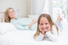Petite fille et mère regardant l'appareil-photo dans le lit Photographie stock