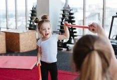 Petite fille et maman faisant des exercices avec des bâtons Photographie stock