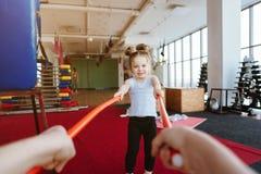 Petite fille et maman faisant des exercices avec des bâtons Photos stock