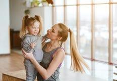 Petite fille et maman posant sur l'appareil-photo Images stock