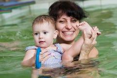 Petite fille et mothe dans la natation Image libre de droits