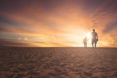 Petite fille et père marchant sur le sable Photos stock