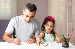 Petite fille et père Drawing Pictures Together Image stock