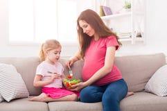 Petite fille et sa maman mangeant de la salade à la maison photographie stock