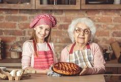 Petite-fille et sa mamie avec le tarte de fruit Images stock