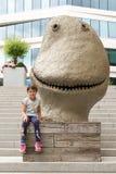 Petite fille et sculpture drôle sur les escaliers chez Aker Brygge, Oslo, Norvège Photos libres de droits