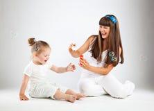 Petite fille et ses bulles de soufflement de mère photographie stock libre de droits