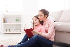 Petite fille et son livre de lecture de maman à la maison Photographie stock libre de droits