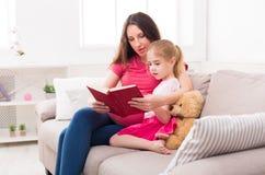 Petite fille et son livre de lecture de maman à la maison Photos libres de droits