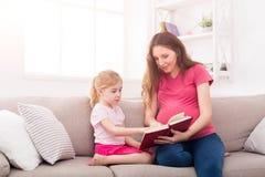 Petite fille et son livre de lecture de maman à la maison Photo stock