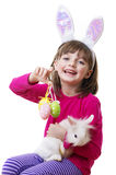 Petite fille avec le masque de lapin de Pâques, tenant un lapin Photo stock