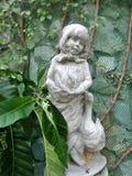 Petite fille et une vigne de sculpture en canard et verte dans le jardin anglais Photographie stock
