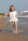 Petite fille exécutant en bas de la plage. Photos stock