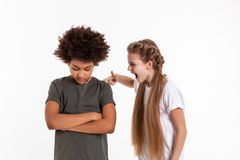 Petite fille expressive folle touchant son ami aux cheveux foncés fané image libre de droits