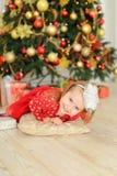 Petite fille féminine se trouvant sur le plancher près de l'arbre de Noël et des présents mignons photographie stock libre de droits